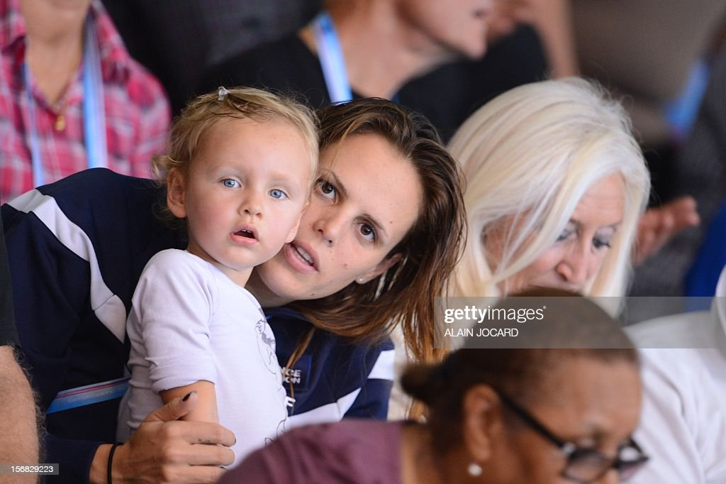 French swimmer Laure Manaudou (C) and her daughter Manon look on during the men's 4x50m medley relay at the European Short Course Swimming Championships on November 22, 2012 in Chartres. AFP PHOTO / ALAIN JOCARD