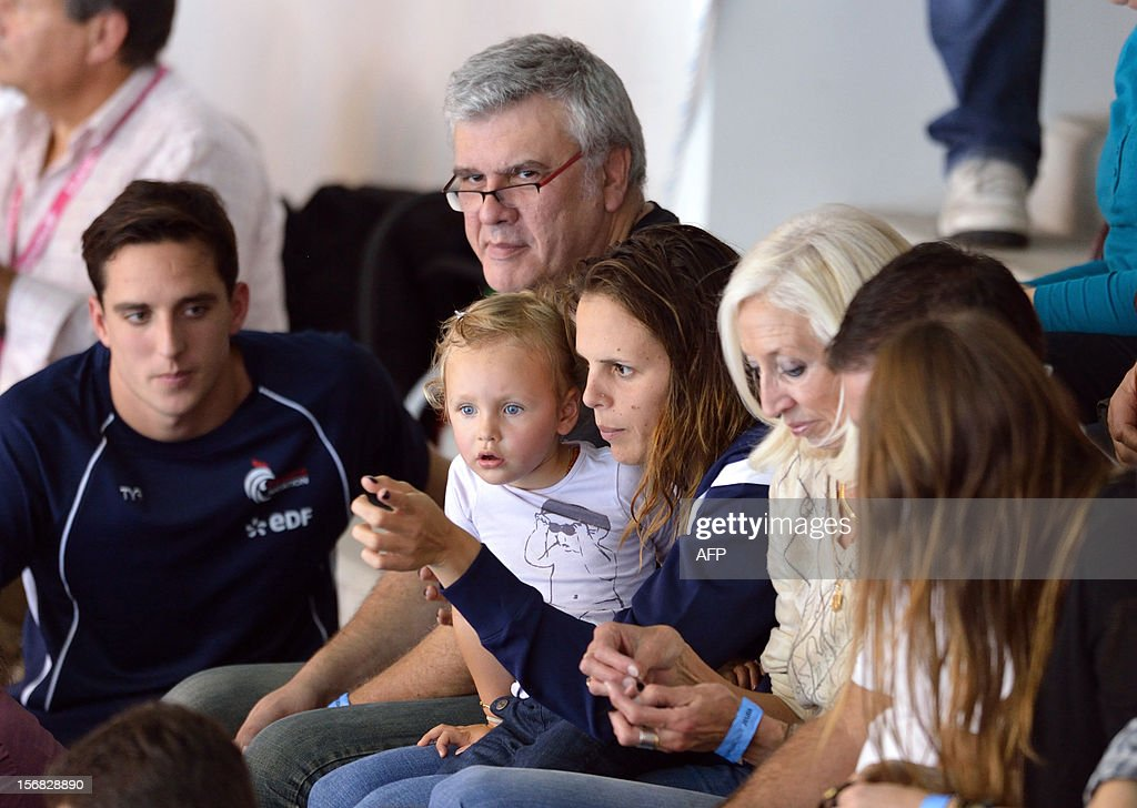 French swimmer Laure Manaudou (C) holds her daughter Manon beside her father Jean-Luc Manaudou (back) and her mother-in-law and mother of French swimmer Frederic Bousquet (C,R) during the men's 4X50m medley relay at the European Swimming Championships on November 22, 2012, in Chartres.