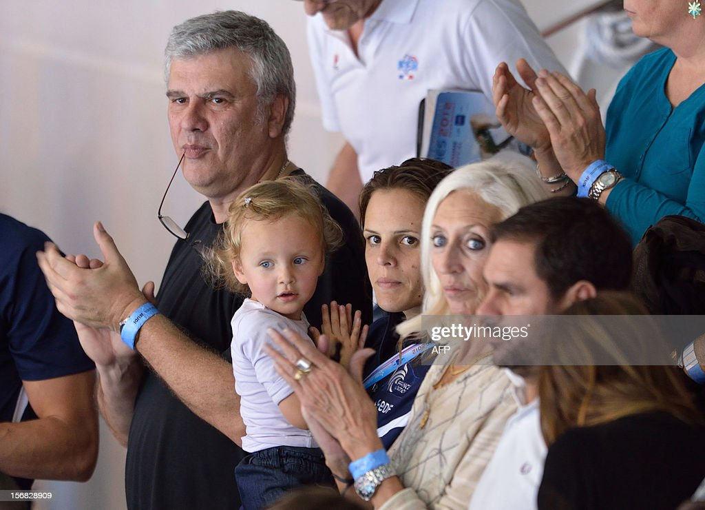French swimmer Laure Manaudou (C) holds her daughter Manon beside her father Jean-Luc Manaudou (C,L) and her mother-in-law and mother of French swimmer Frederic Bousquet (C,R) during the men's 4X50m medley relay at the European Swimming Championships on November 22, 2012, in Chartres.