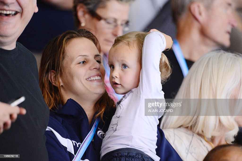 French swimmer Laure Manaudou (2ndL) holds her daughter Manon during the men's 4x50m medley relay at the European Short Course Swimming Championships on November 22, 2012 in Chartres. AFP PHOTO / ALAIN JOCARD