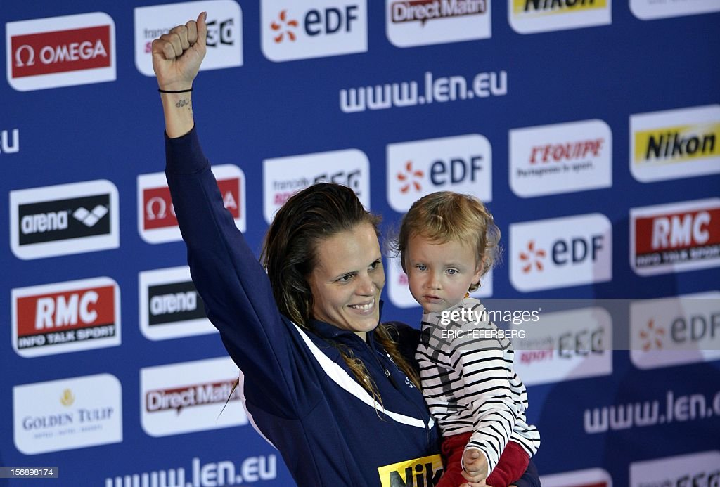 French swimmer Laure Manaudou poses with her girl Manon on the podium after winning the short course women's 50m backstroke event at the European Swimming Championships on November 24, 2012, in Chartres.