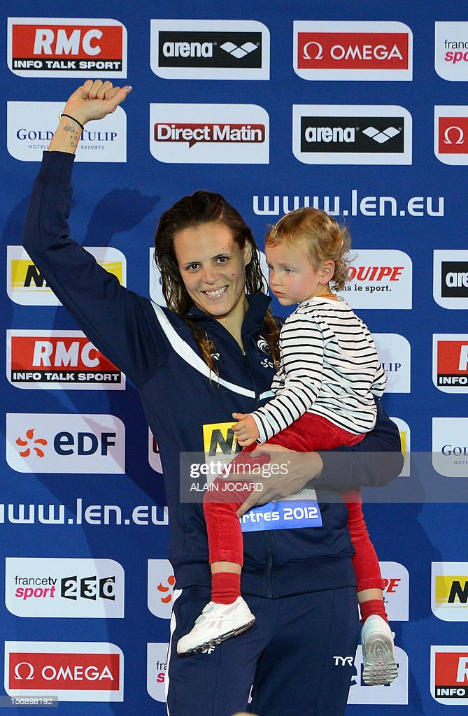 French swimmer Laure Manaudou poses with her girl Manon on the podium after winning the short course women's 50m backstroke event at the European Swimming Championships on November 24, 2012, in Chartres. AFP PHOTO /ALAIN JOCARD