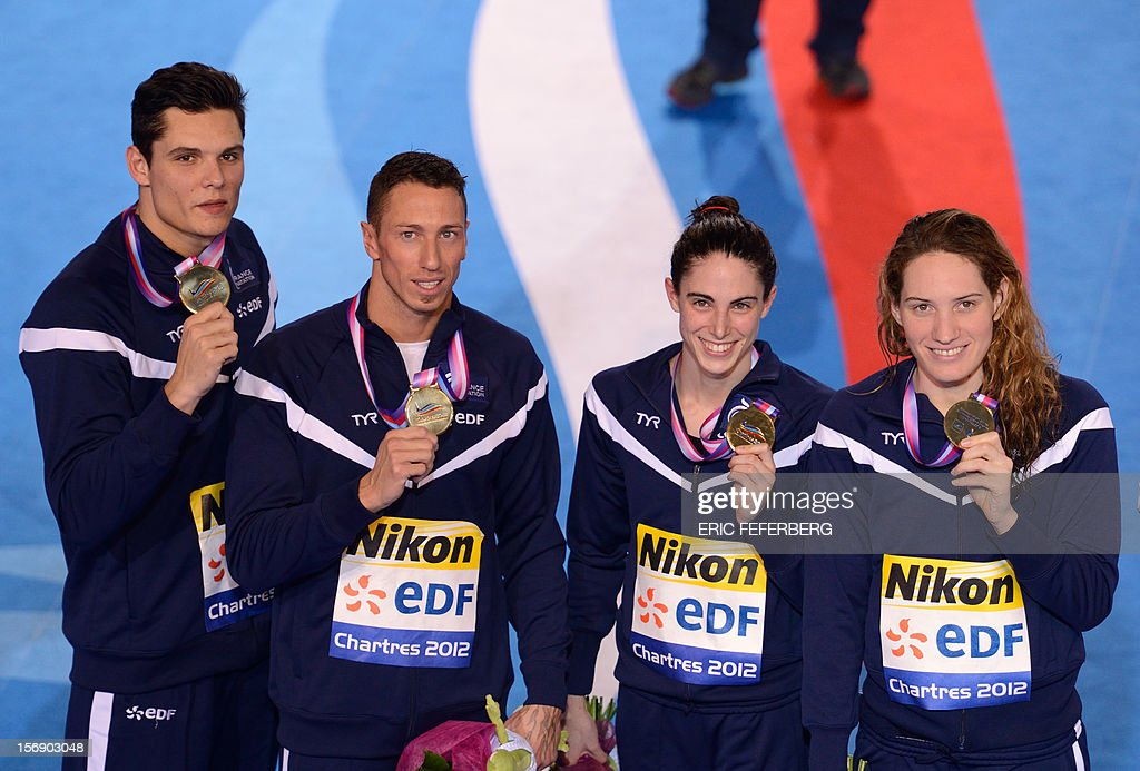 French swimmers Florent Manaudou (L), Frederik Bousquet (2nd L), Anna Sanramans (2nd R), Camille Muffat (R), pose with their gold medals after winning the mixed 4X50m freestyle final at the European Swimming Championships on November 24, 2012, in Chartres. AFP PHOTO / ERIC FEFERBERG