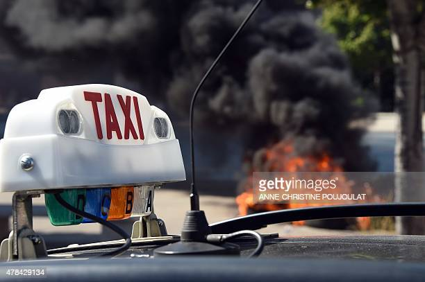 French Taxi drivers burn tires during a protest in the southern city of Marseille on June 25 2015 as they demonstrate against UberPOP a popular taxi...
