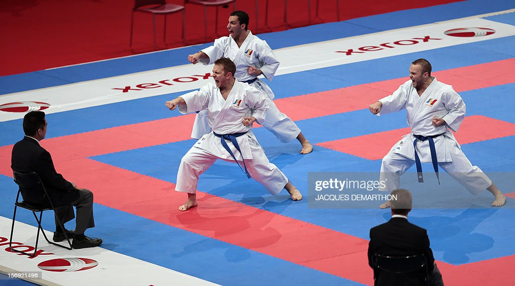 French team members, Jonathan Plagnol (L), Romain Lacoste (C) and Jonathan Maruani, compete against Turkey on November 25, 2012 during the men's team kata semi-finals of the Karate world championships at the POPB stadium in Paris.