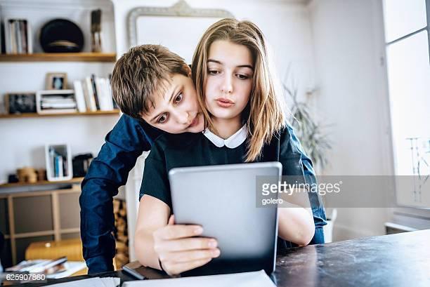 french teenage boy looks over sisters shoulder on digital tablet