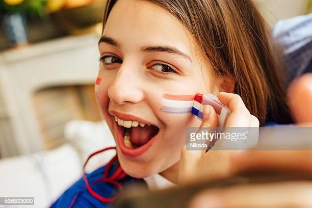 français adolescente avec de la peinture sur visage tricolore et prenant un selfie