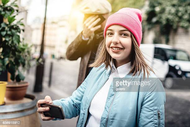 french teenage girl with pink beanie smiling into camera