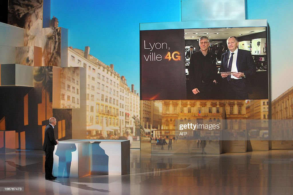 French telecom group Orange-France Telecom CEO, Stephane Richard (L) speaks in front of a giant screen during a press conference to unveil telecom provider Orange latest innovations on November 21, 2012 in Saint-Denis, suburbs of Paris. Richard annouced that the super-fast 4G mobile Internet service will be available for companies on November 22 in the French cities Lyon, Nantes and Lille.