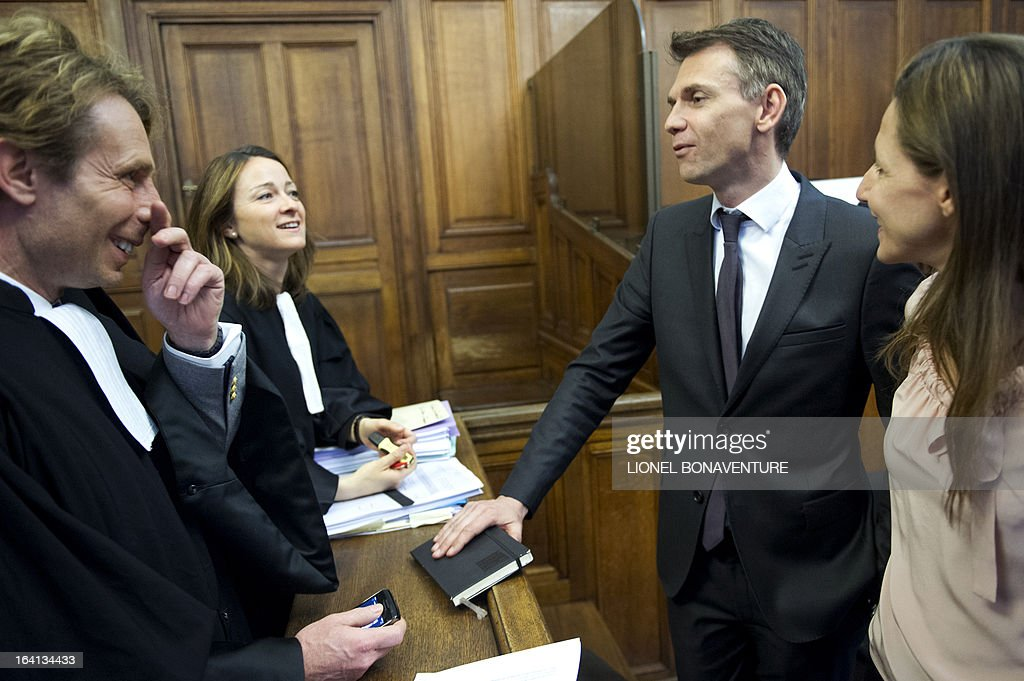 French television journalists Christophe Jakubyszyn (2ndR) and Alix Bouilhaguet (R), speak with their lawyers as they wait for the start of their trial on March 20, 2013 at the Paris' courthouse, after Valerie Trierweiler, the president's 47-year-old partner, suied them for defamation and invasion of privacy, seeking 85,000 euros ($110,000) in damages and court costs, for their book of 'La Frondeuse' (The Rebel). As the trial opened on Monday, it emerged that Hollande sent a letter -- but not on paper with the presidential letterhead -- to the court denying an assertion in the book that he had reached out to the right in the mid-1990s. There was no official reaction from Hollande, but a source close to the president said he was in no way trying to influence the court and was simply providing testimony in the case. AFP PHOTO / LIONEL BONAVENTURE