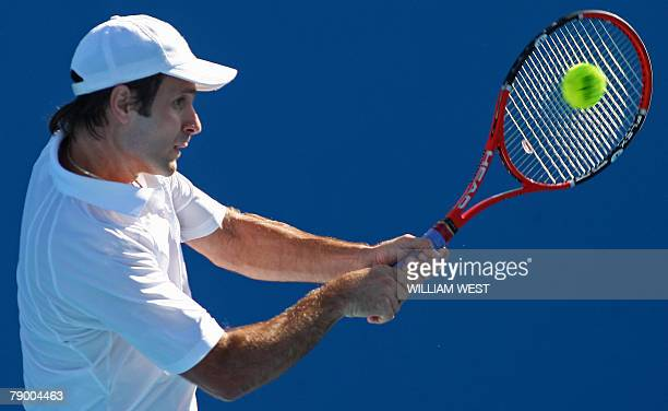 French tennis player Fabrice Santoro plays a return during his mens singles match against US opponent John Isner at the Australian Open tennis...