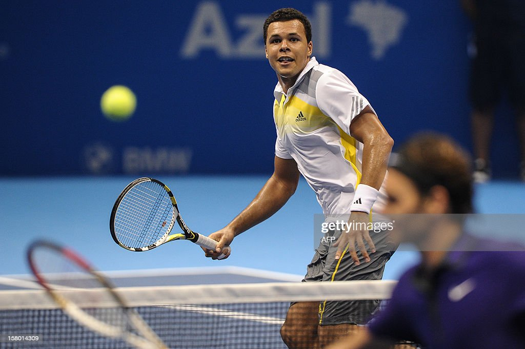 French tennis player French Jo-Wilfried Tsonga plays against Swiss Roger Federer during an exhibition match held at the Ibirapuera Gymnasium in Sao Paulo, Brazil, on December 8, 2012. AFP PHOTO/Yasuyoshi CHIBA