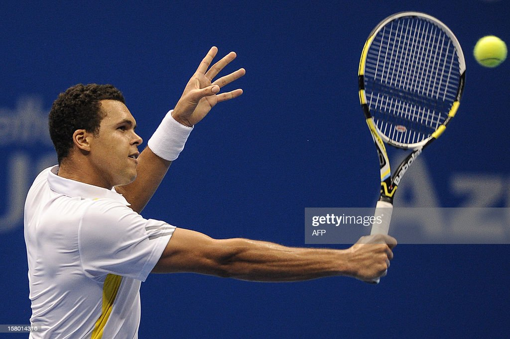 French tennis player French Jo-Wilfried Tsonga returns a shot against Swiss Roger Federer during an exhibition match held at the Ibirapuera Gymnasium in Sao Paulo, Brazil, on December 8, 2012. AFP PHOTO/Yasuyoshi CHIBA