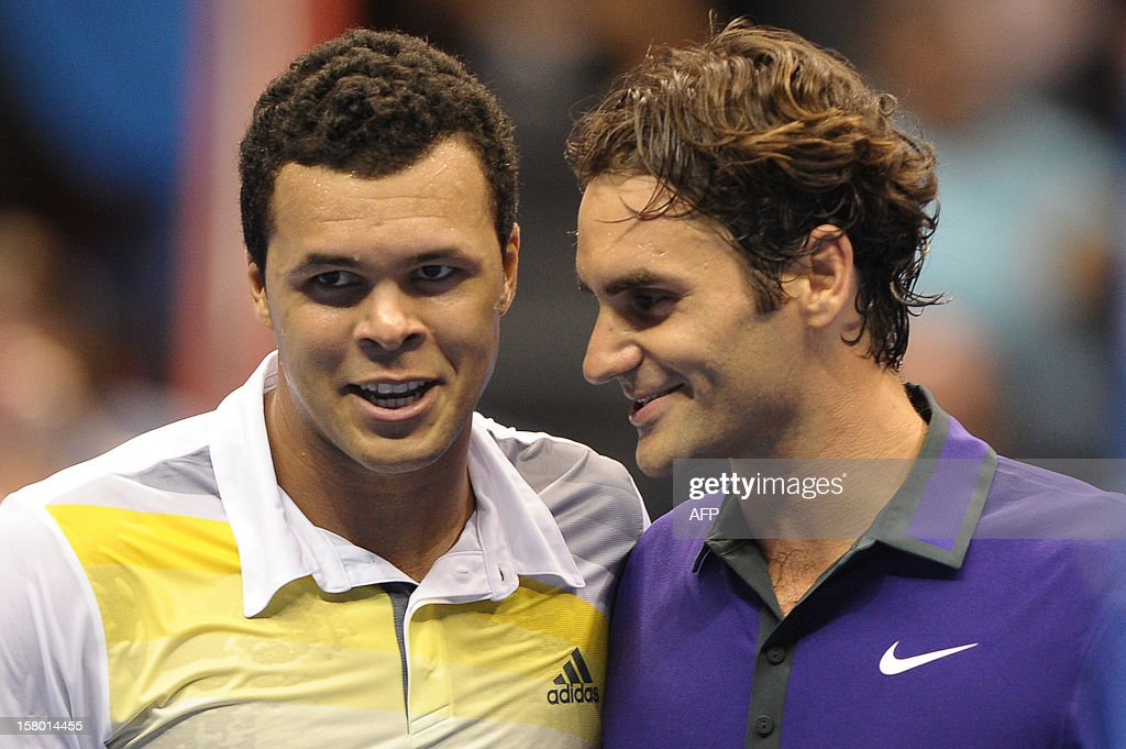 French tennis player French Jo-Wilfried Tsonga (L) speaks with Swiss Roger Federer after their exhibition match held at the Ibirapuera Gymnasium in Sao Paulo, Brazil, on December 8, 2012. AFP PHOTO/Yasuyoshi CHIBA