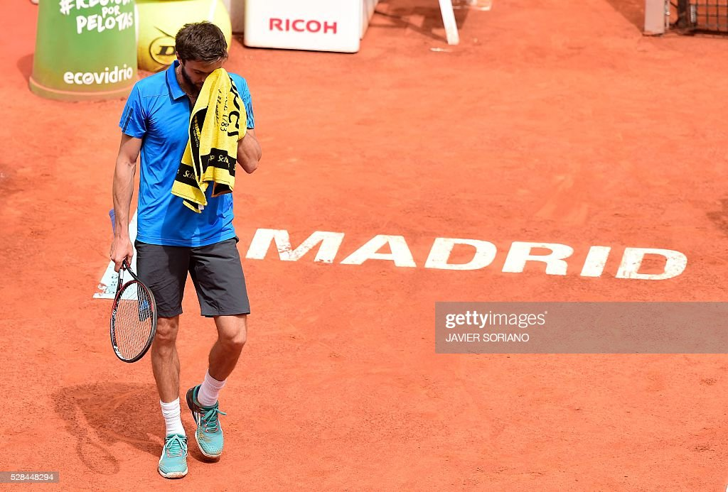 French tennis player Gilles Simon wipes his face during the Madrid Open tournament at the Caja Magica (Magic Box) sports complex in Madrid on May 5, 2016. / AFP / JAVIER