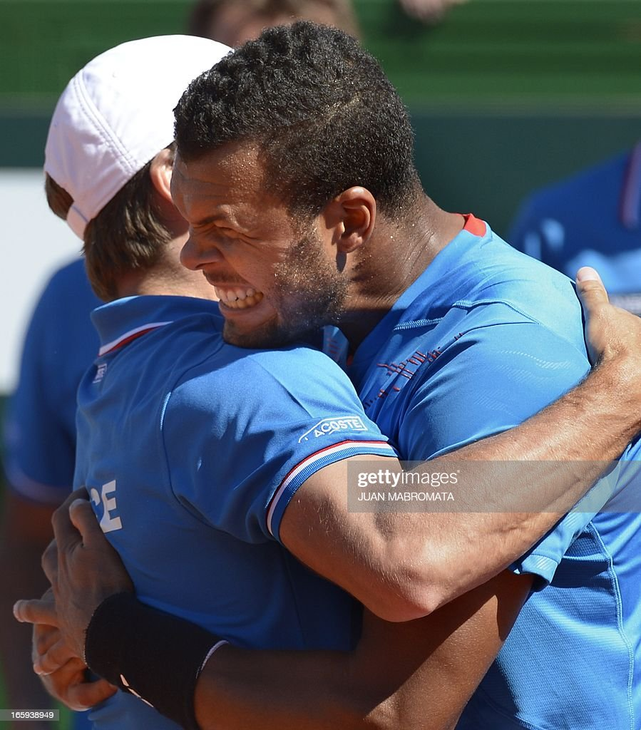 French tennis player Jo-Wilfried Tsonga (R) celebrates with team captain Arnaud Clement after beating Argentine tennis player Juan Monaco in the Davis Cup quarterfinals tennis match at Mary Teran de Weiss stadium in Roca Park in Buenos Aires on April 7, 2013. Tsonga won 6-3, 6-3, 6-0.