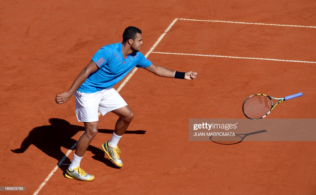 French tennis player Jo-Wilfried Tsonga drops his racket while returning a ball to Argentine tennis player Juan Monaco during the Davis Cup quarterfinals tennis match at Mary Teran de Weiss stadium in Roca Park in Buenos Aires on April 7, 2013.