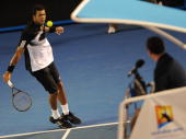 French tennis player JoWilfried Tsonga is watched by the umpire as he plays a backhand stroke during his mens singles semifinal match against Spanish...