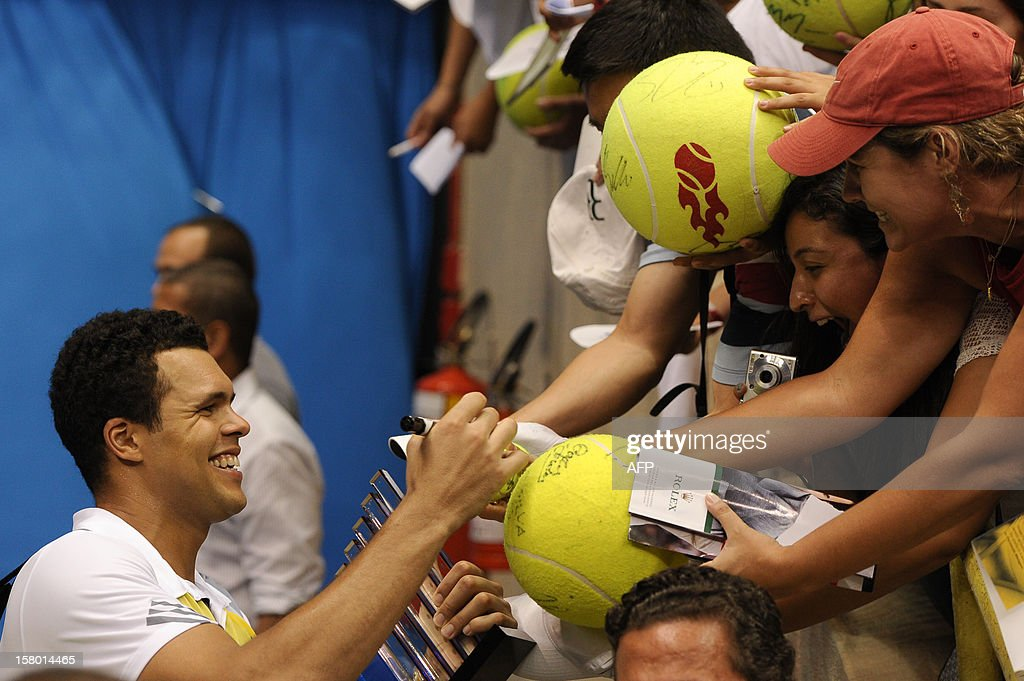 French tennis player Jo-Wilfried Tsonga signs autographs to fans after an exhibition match against Swiss Roger Federer held at the Ibirapuera Gymnasium in Sao Paulo, Brazil, on December 8, 2012. AFP PHOTO/Yasuyoshi CHIBA