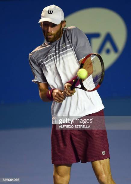 French tennis player Stephane Robert returns against Belgian tennis player David Goffin during the first day of the Mexican Tennis Open in Acapulco...