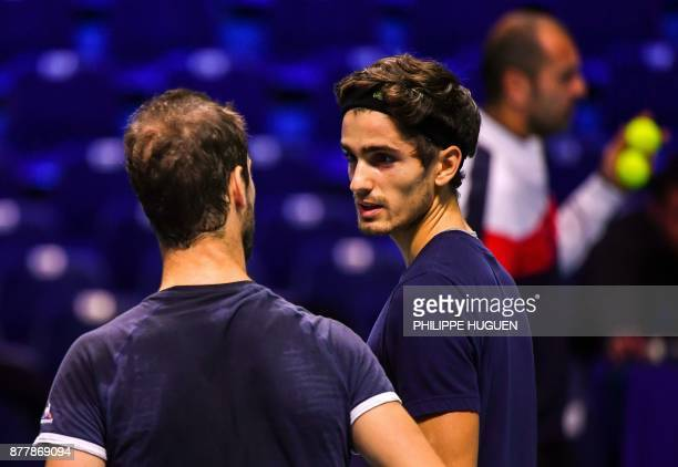 French tennis players PierreHugues Herbert and Richard Gasquet talk during a training session on November 23 2017 at the PierreMauroy stadium in...
