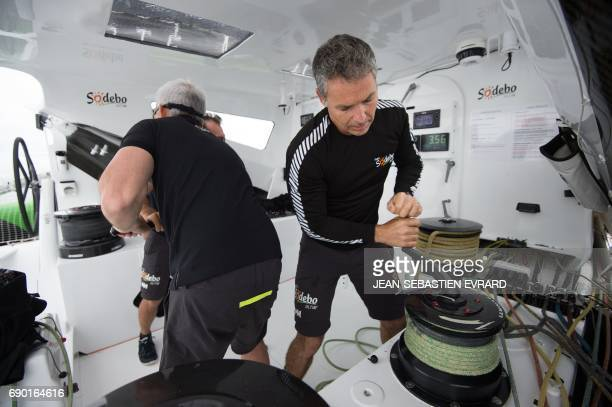 French Thierry Briend sails aboard the multihull 'Sodebo Ultim' of Thomas Coville on May 30 2017 off La TrinitesurMer western France Coville prepares...