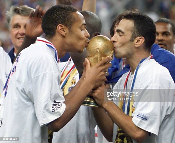 French Thierry Henry and Youri Djorkaeff kiss the FIFA trophy as coach Aime Jacquet looks on 12 July at the Stade de France in SaintDenis near Paris...