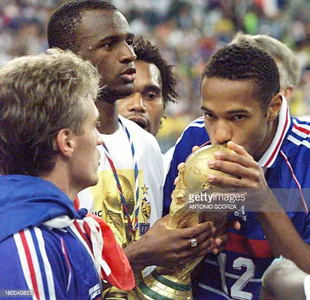 French Thierry Henry kisses the FIFA trophy as teammates Patrick Vieira and captain Didier Deschamps look on 12 July at the Stade de France in...
