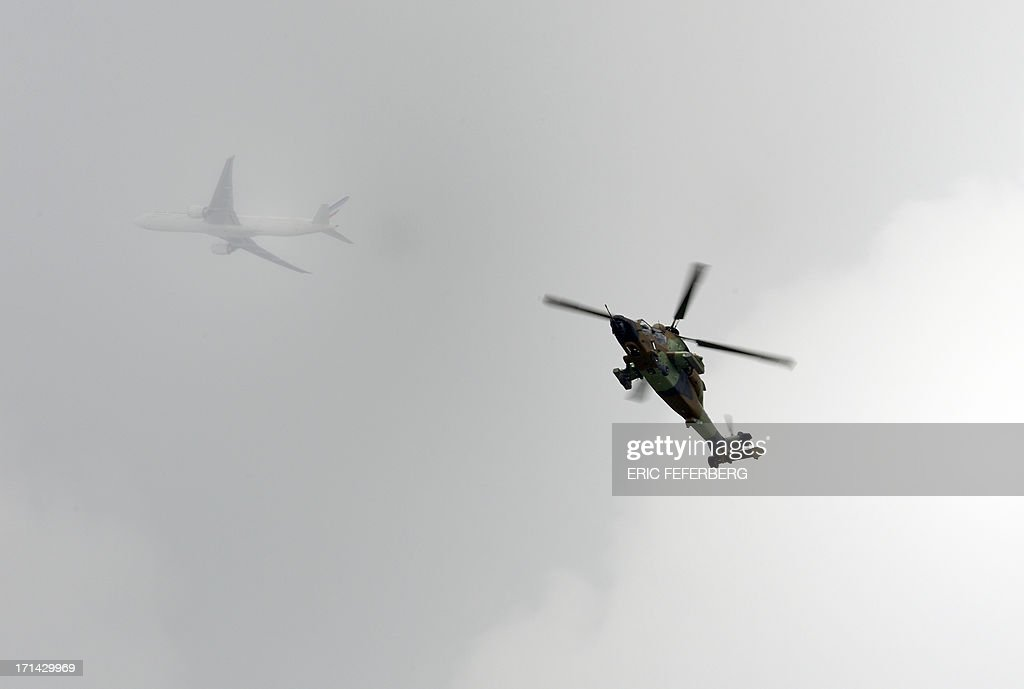 A French Tiger helicopter performs while an Air France commercial flight passes in the background at Le Bourget airport, near Paris on June 23, 2013 on the last day of the 50th International Paris Air show.