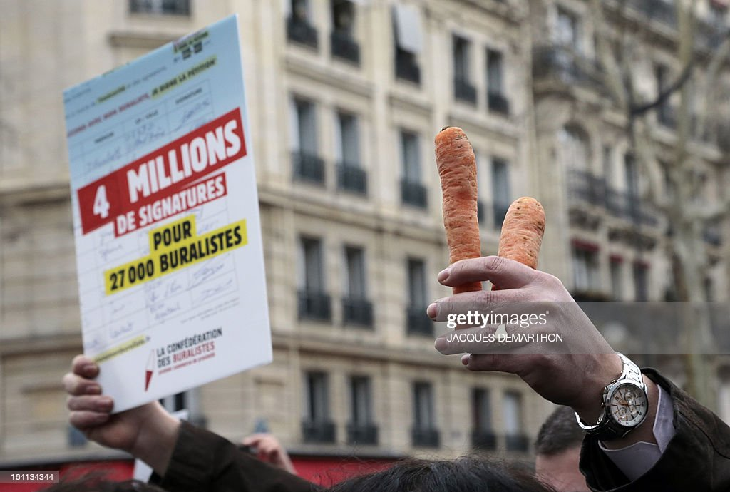 French tobacconist raise carrots as they take part in a demonstration on March 20, 2013 near the Health ministry in Paris, to present a nationwide petition protesting against the last tobacco price's increase decided by the government and Brussels' recent health recommendations.