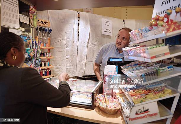 A French tobacconist sells a cigarette pack in front of a white sheet with placards as part of a national day of protest as the government is...