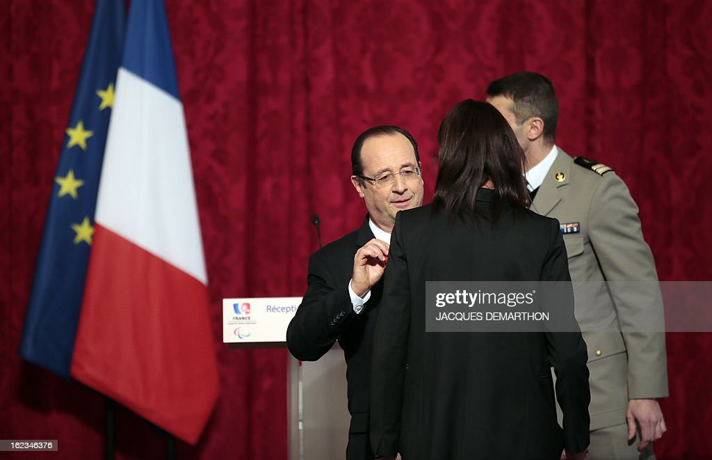 French track and field athlete and 2012 London Paralympic Games gold medalist Assia El Hannouni receives the Legion d'Honneur decoration from France's President Francois Hollande (C) during an awards ceremony at the Elysee Palace on February 22, 2013 in Paris. AFP PHOTO / POOL / JACQUES DEMARTHON