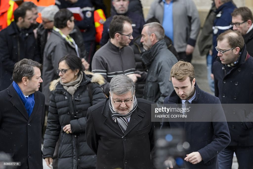 French Transports Minister Alain Vidalies (C) walks on February 10, 2016, in Montbenoit near Pontarlier, eastern France, after a school bus accident. Two teenagers were killed and four other persons slightly injured, after the school bus went off the road presumably due to bad weather conditions, according to the police. The accident occurred at around 7:30 a.m. on Wednesday in Montbenoit, when the bus was on its way to the Lucie Aubrac college in the Doubs region. / AFP / FABRICE COFFRINI