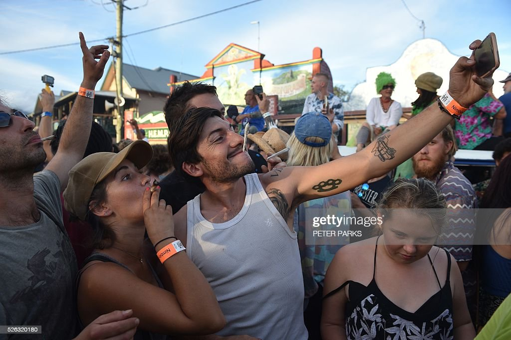 French travellers at the Mardi Grass festival take selfies during the Global Marijuana March in the eastern Australian town of Nimbin on April 30, 2016. . The festival, an annual cannabis law reform protest and gathering, attracts thousands of revellers from across Australia and around the world. / AFP / PETER