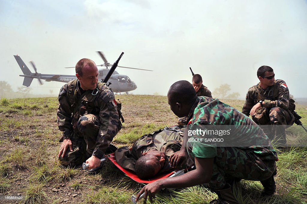 French troops from the 'Licorne' operation based in Abidjan and a soldier (R, foreground) from Ivory Coast's Republican Forces (FRCI) wait before carrying a soldier into a helicopter during a military exercise on April 6, 2013 in Lomo Sud, about 180 km north of Abidjan. FRCI soldiers are members of the Ivorian logistics battalion due to join the African-led MISMA forces in Mali. AFP PHOTO / ISSOUF SANOGO
