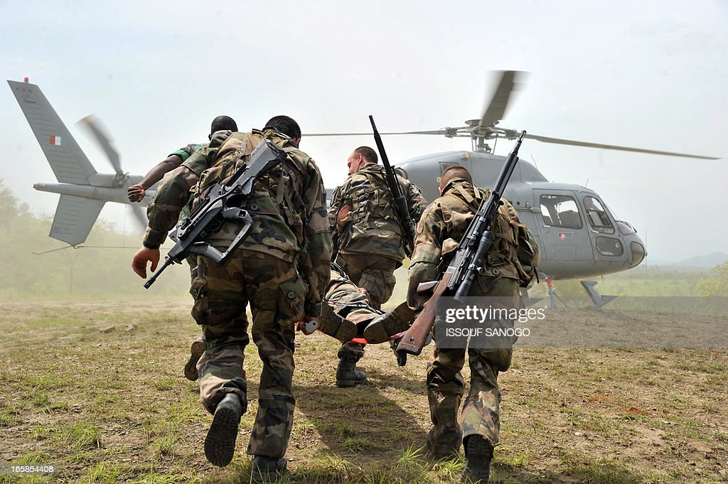 French troops from the 'Licorne' operation based in Abidjan and a soldier from Ivory Coast's Republican Forces (FRCI) carry a soldier back into a helicopter during a military exercise on April 6, 2013 in Lomo Sud, about 180 km north of Abidjan. FRCI soldiers are members of the Ivorian logistics battalion due to join the African-led MISMA forces in Mali.