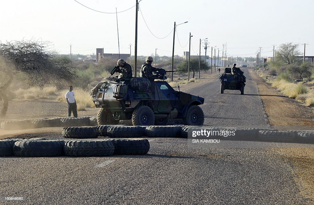 French troops pass a road block on the airport road in Gao on February 4, 2013 . Schools reopened Monday in Gao in northern Mali after French and Malian troops moved in and armed Islamists who had held the town for seven months fled. AFP PHOTO / SIA KAMBOU