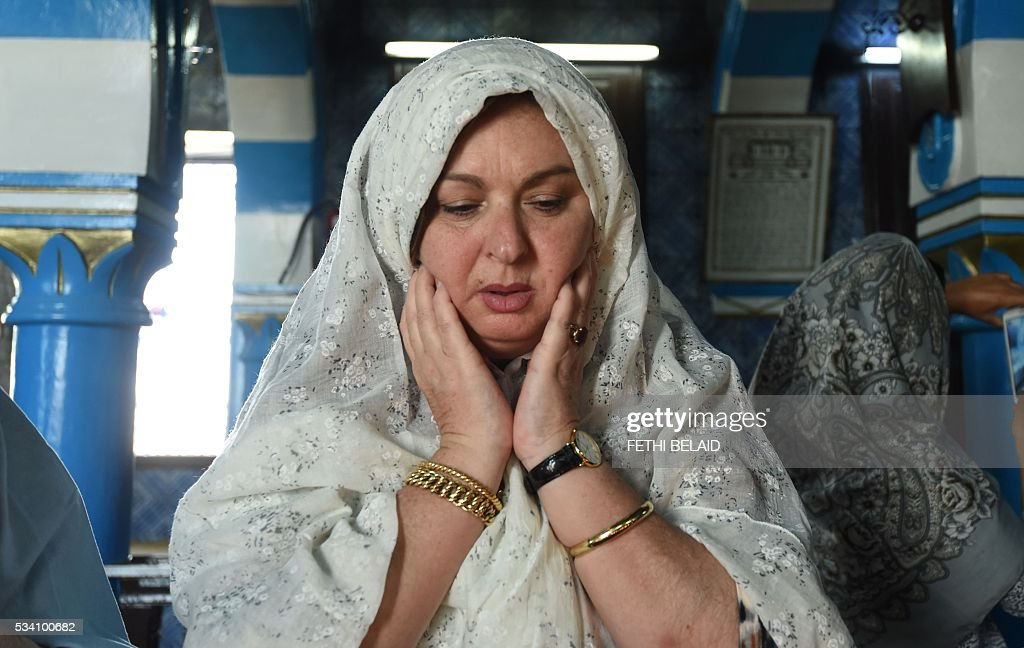 A French Tunisian Jewish woman prays at the Ghriba synagogue in the Tunisian resort island of Djerba during the annual Jewish pilgrimage on May 25, 2016. Pilgrims arrived at Tunisia's Ghriba synagogue, the oldest in Africa, expressing hope that this year would mark a turning point for the ritual despite a rise in Islamist unrest since the 2011 revolution. Djerba is home to one of the last Jewish communities in the Arab world. / AFP / FETHI