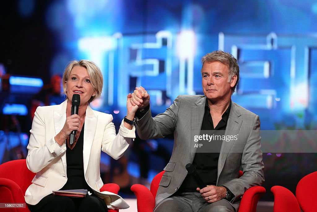 French TV host and Master of Ceremonies of the 2012 Telethon edition, Sophie Davant, (L) and French comic and godfather of the 2012 Telethon's edition, Franck Dubosc, clasp hands during the 26th Telethon, France's biggest annual fund-raising event carried out over 30 hours of live television transmission, on December 8, 2012 in Saint-Denis, north of Paris. The event aims at collecting funds for research on genetic diseases such as myopathy, a neuromuscular disease.