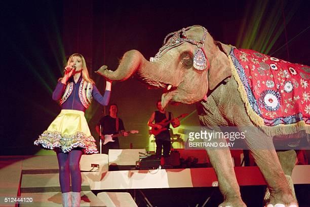 French TV host and singer Dorothée flanked by an elephant performs on January 19 1992 at the Bercy concert hall in Paris / AFP / Bertrand GUAY