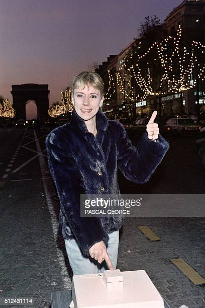 French TV host and singer Frederique Hoschede better known as Dorothée turns on the Christmas lights on the Champs Elysees in Paris on November 28...
