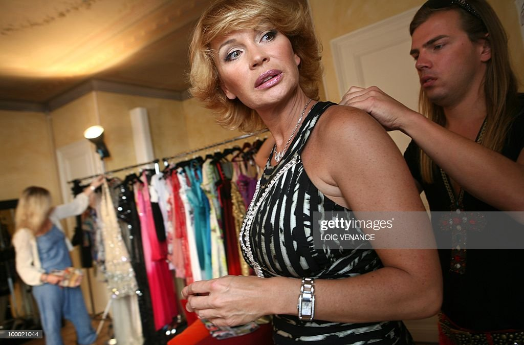 French TV host Marlene Mourreau tries a dress designed by French Christophe Guillarme (R) as she prepares to walk on the red carpet at the 63rd Cannes Film Festival on May 20, 2010 in Cannes.
