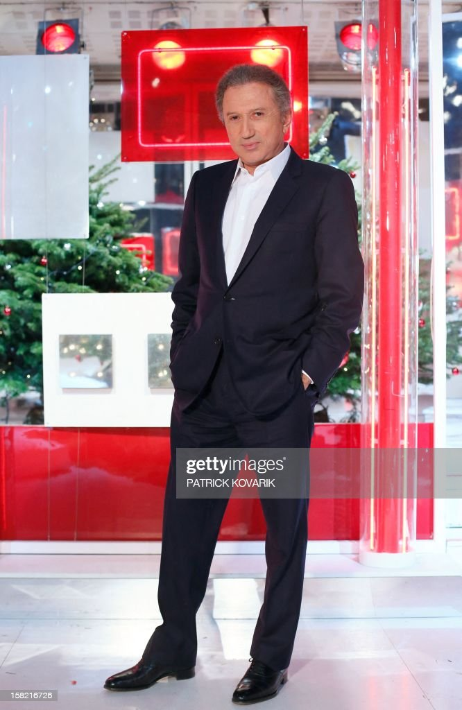 French TV host Michel Drucker poses on the set of the French TV France 2 show, 'Vivement Dimanche', on December 11, 2012 in Paris. AFP PHOTO / PATRICK KOVARIK
