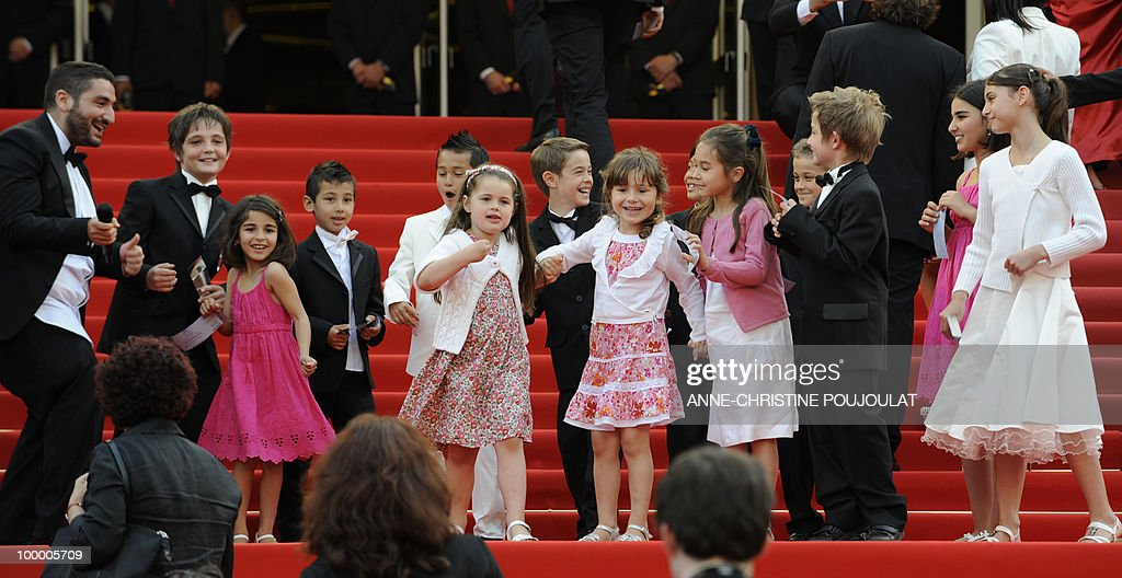 French TV host Mouloud Achour (L) arrives with a group of children for the screening of 'Poetry' presented in competition at the 63rd Cannes Film Festival on May 19, 2010 in Cannes.