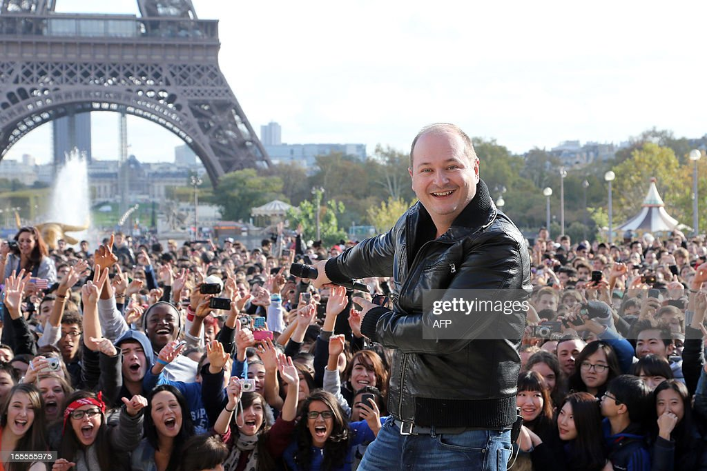French TV host Sebastien Cauet poses ' in front of a crowd during a flash mob by South Korean rapper Psy on November 5, 2012 in Paris. The video to 'Gangnam Style' went viral after its July release, becoming the second most viewed clip in YouTube history, where it has notched up more than 650 million hits despite being sung almost entirely in Korean.