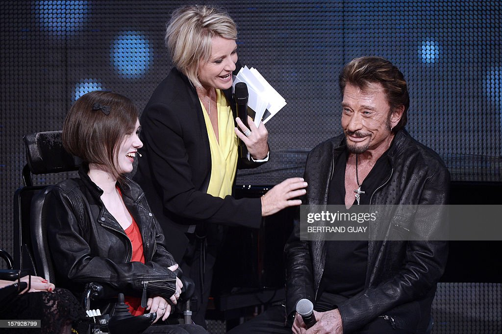French TV hosts Sophie Davant (C), French singer Johnny Hallyday (R) and Jeanne (L) attend the 26th Telethon, France's biggest annual fund-raising event during 30 hours of live television transmission, on December 7, 2012 in Saint-Denis, north of Paris. The event, aiming at collecting funds for research on genetic diseases such as myopathy, a neuromuscular disease, will take place on December 7 and 8, 2012. AFP PHOTO / BERTRAND GUAY