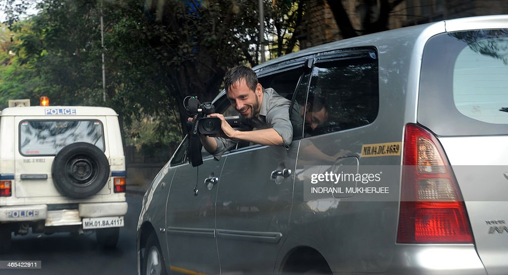 A French TV news channel cameraman leans out of his car as he follows the convoy of cars of former partner of French President Francois Hollande, Valerie Trierweiler on her way to visit the children's ward at the Sion hospital in Mumbai on January 27, 2014. France's former first lady Valerie Trierweiler tried to shrug off the furore over her split from President Francois Hollande on a trip to India, telling a media scrum she was feeling 'very good'.
