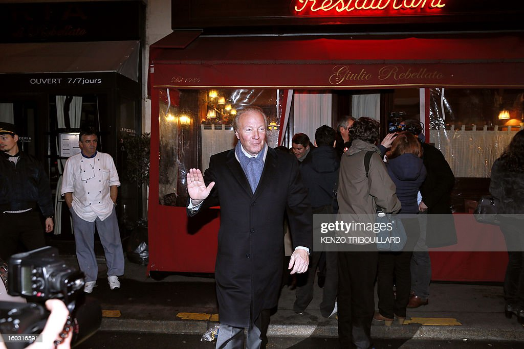 French UMP opposition right-wing party member of the European Parliament Brice Hortefeux waves as he leaves the Rebelatto restaurant after a dinner with relatives to celebrate forme French president Nicolas Sarkozy's 58th birthday, on January 28, 2013 in Paris. AFP PHOTO KENZO TRIBOUILLARD
