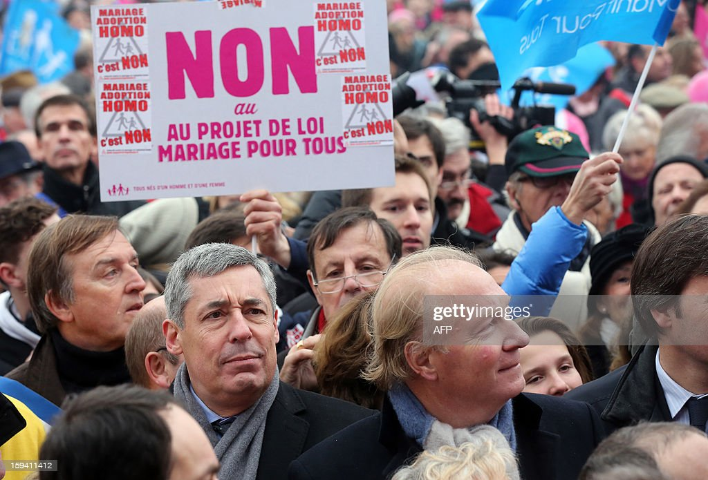 French UMP opposition right-wing party members of parliament Henri Guaino (2ndL) and Brice Hortefeux (R) take part in a protest against same-sex marriage on January 13, 2013 in Paris. Tens of thousands march in Paris on January 13 to denounce government plans to legalise same-sex marriage and adoption which have angered many Catholics and Muslims, France's two main faiths, as well as the right-wing opposition. The French parliament is to debate the bill -- one of the key electoral pledges of Socialist President -- at the end of this month. AFP PHOTO / THOMAS SAMSON