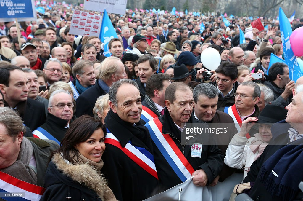 French UMP opposition right-wing party president Jean-Francois Cope (3rdL) and his wife Nadia Hamama (2ndL), UMP member of parliament Patrick Ollier (C) take part in a protest against same-sex marriage on January 13, 2013 in Paris. Tens of thousands march in Paris on January 13 to denounce government plans to legalise same-sex marriage and adoption which have angered many Catholics and Muslims, France's two main faiths, as well as the right-wing opposition. The French parliament is to debate the bill -- one of the key electoral pledges of Socialist President -- at the end of this month.